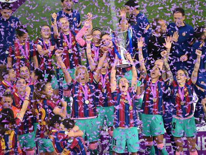 Alexia Putellas, entre Hamraoui y Jennifer Hermoso, levanta el trofeo que acredita al Barça como campeón de Europa.
