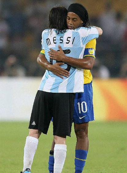 Messi y Ronaldinho, que fueron compañeros en el Barcelona, se abrazan al término del partido.
