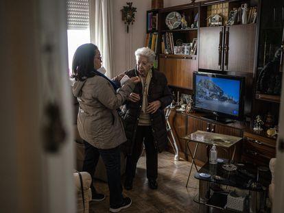 Dirsia González ayuda a Isabel Martin, de 99 años, a colocarse la mascarilla para ir al centro de salud a que la vacunen contra la covid-19.