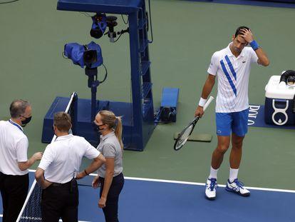 Djokovic observa las deliberaciones de los responsables del arbitraje antes de conocer la descalificación.