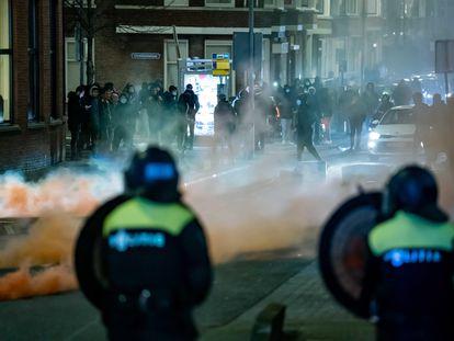 Policías antidisturbios, ante grupos de jóvenes, este lunes en Róterdam.