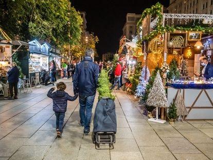 Un hombre con su hijo en el Mercado de Navidad de Santa Lucía en Barcelona.