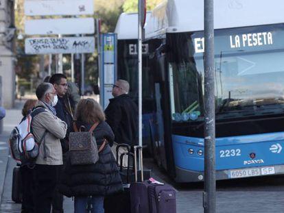 Varias personas esperan el autobús en una parada de la EMT en Cibeles, en Madrid.