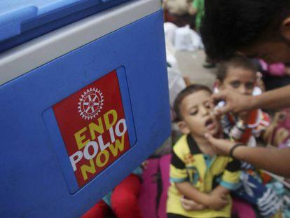 Un trabajador sanitario administra la vacuna de la polio a un niño, durante la campaña realizada en Karachi (Pakistán).
