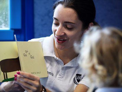 Una alumna mayor cuenta un cuento a una alumna de infantil en uno de los colegios SEK