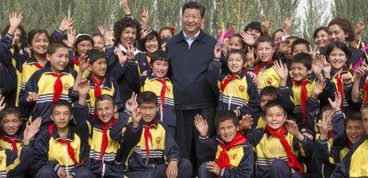 El presidente Xi Jinping posa con unos estudiantes durante su visita a la región de Xinjiang.