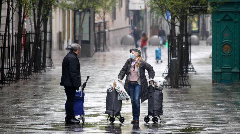 Una mujer protegida con mascarilla y guantes sanitarios realiza compras durante el sexto día del estado de alarma por coronavirus, en Madrid.