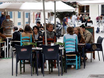 Varias personas disfrutan en una terraza en Valencia.