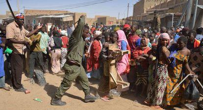 Un soldado maliense intenta dispersar una multitud que asalta una tienda perteneciente a un vecino árabe, en Tombuctú.