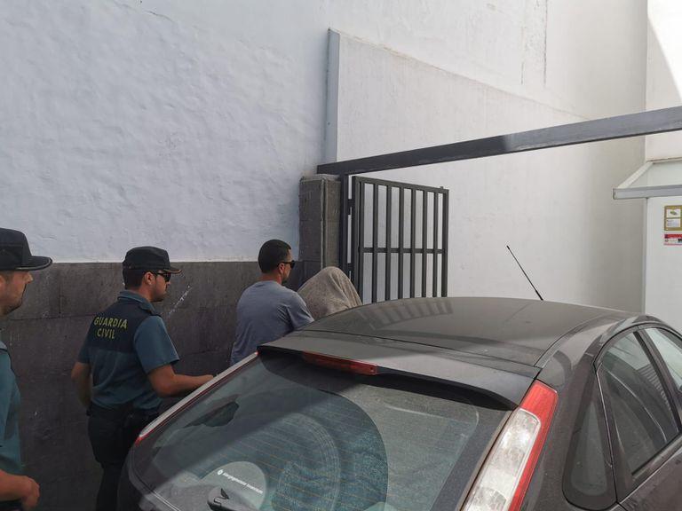 Uno de los presuntos agresores se tapa en su entrada al juzgado de instrucción de los Llanos de Aridane (La Palma). EL PAÍS