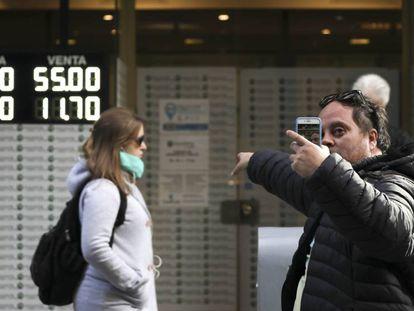 Un hombre se hace un selfi frente a una casa de cambio, este lunes en Buenos Aires.