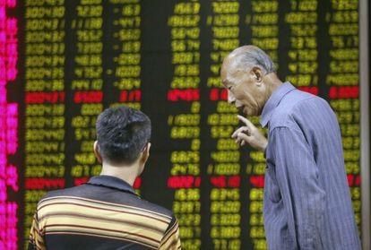 Dos inversores conversan en Pekín ante los paneles de cotización