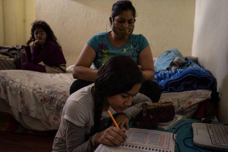 Dayanira Blanco y su hija Sara hacen las tareas que su maestra le envía semanalmente por WhatsApp durante el confinamiento en Ecuador.