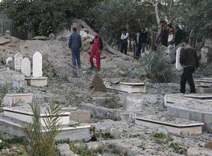Un grupo de palestinos observa los daños que ha dejado el bombardeo en el principal cementerio de la ciudad de Gaza.