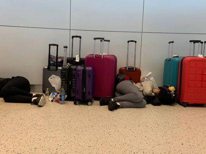 Dos pasajeros duermen en el interior del aeropuerto JFK, en Nueva York (Estados Unidos), tras el retraso de varios días sufrido en el vuelo 2036 de British Airways.