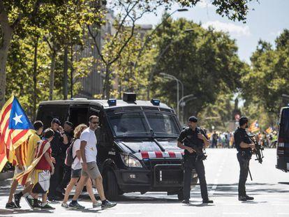 Un par de furgones de los Mossos d'Esquadra vigilan en la Gran Via la manifestación de ayer en Barcelona.