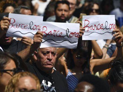Tres personas portan el diseño creado por Amat en la concentración de personas tras el atentado de La Rambla.