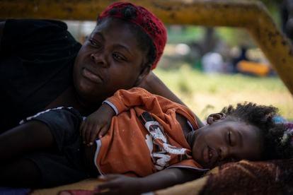 Sonia Jeudy y su hijo descansan sobre un colchón en el suelo.