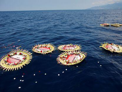 Coronas de flores con los nombres de la tripulación a bordo del submarino de la Armada indonesia 'KRI Nanggala' flotan en el mar en un homenaje por las víctimas del accidente.
