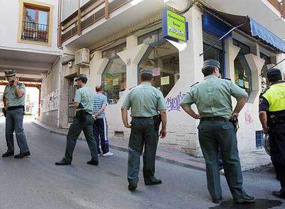 Cuatro agentes de la Guardia Civil y un policía local rodean la tienda donde se produjo el asesinato.