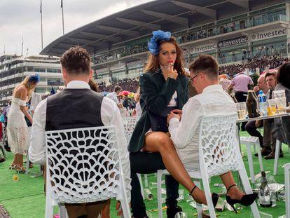 Una mujer fuma sentada sobre el regazo de un hombre en el Ladies' Day (día de las mujeres) en las carreras de Epsom, que tradicionalmente se celebra el primer viernes de junio en el condado de Surrey.