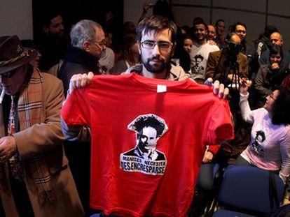 Un joven muestra una camiseta contra la crispación política.