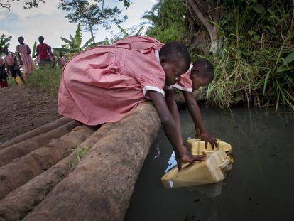 Robina, de 9 años, y su amiga Charity, de 12, recogen agua en Nmamyumba (Uganda).