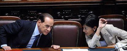 Berlusconi conversa en el Parlamento con su ministra de Igualdad de Oportunidades, Mara Carfagna, durante la investidura del Gobierno el 14 de mayo.