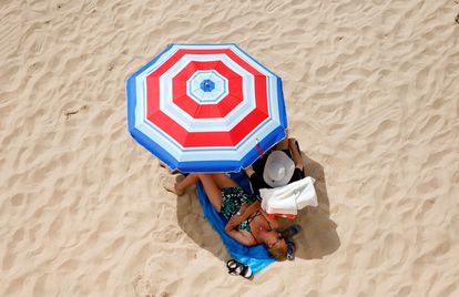 Dos turistas disfrutan del sol en la playa de Levante de Benidorm.