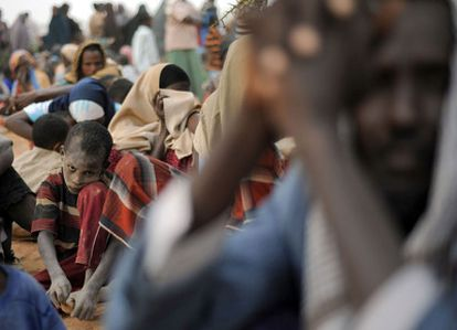 Un niño, con el rostro lleno de arena, espera junto a otros refugiados somalíes a formalizar en registro en el campo de refugiados de Dagahaley.