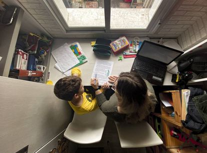 Un niño estudia y hace los deberes en casa con la ayuda de su madre.