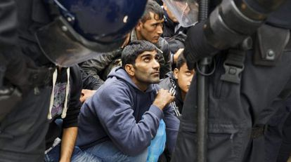 Varios refugiados esperan en la entrada del centro de acogida en Croacia.