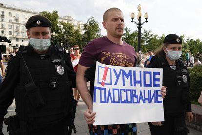 """La policía rusa detiene a un activista con una pancarta en la que se lee """"Voto inteligente"""", el pasado agosto en Moscú."""
