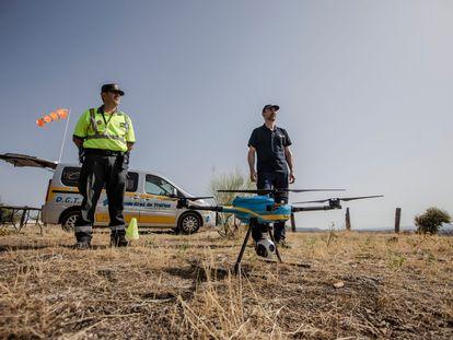 El guardia civil Javier (izq) y Javier Ibañez, operador de drones de la Dirección General de Tránsito posan junto a uno de los drones utilizados para supervisar la circulación. 13 de agosto, 2021. Villa del Prado. Comunidad de Madrid. Foto: Saúl Ruiz.