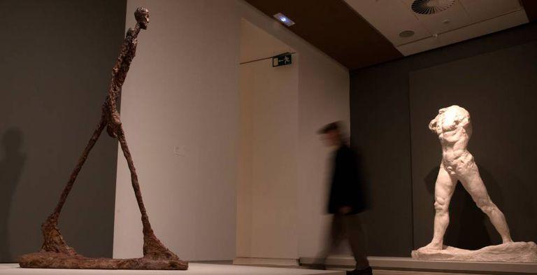 'El hombre que camina' de Giacometti (a la izquierda), frente al 'Hombre que camina' de Rodin en la exposición de la Fundación Mapfre 'Rodin-Giacometti'.