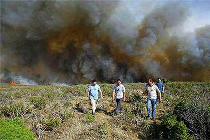 Varios hombres se alejan del fuego en la localidad guadalajareña de Santa María del Espino.