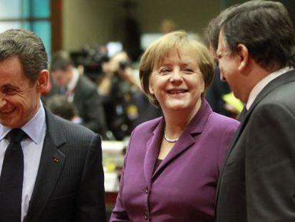 Merkel habla con Sarkozy (dcha) y Durao Barroso.