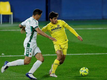 Gerard Moreno protege el balón ante el defensa del Elche Diego González este domingo en La Cerámica.