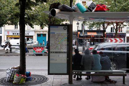 Migrantes esperan bajo la parada de autobús durante la evacuación del campamento improvisado en París.