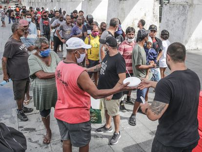 Voluntarios distribuyen comida a personas pobres de Río de Janeiro, en abril.
