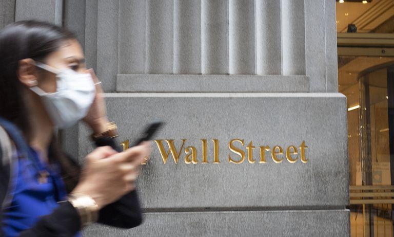 Una mujer con mascarilla pasa frente al edificio de Wall Street en Nueva York.