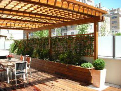 Porche con techo, pavimento y jardinera de madera de ipe, de Ábaco Espacios en Madera.
