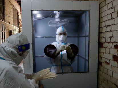 Trabajadores sanitarios se preparan para tomar muestras para el diagnóstico rápido de la covid-19 en un centro comunitario de cuarentena en Yangon, Myanmar.