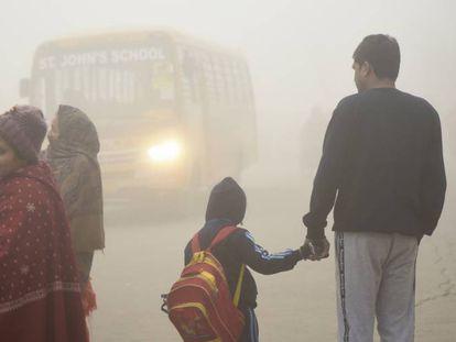 Un niño y su padre esperan el autobús del colegio en Nueva Delhi, entre la polución causado por el polvo, las emisiones de las fábricas y la quema de carbón y basura para calentarse en invierno.