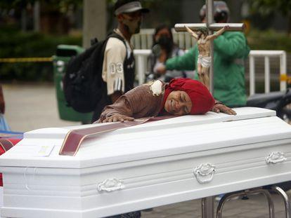 AME145. MEDELLÍN (COLOMBIA), 24/08/2020.- Una mujer abraza uno de los ataúdes colocados en la calle para rechazar las recientes masacres en el país hoy, en Medellín (Colombia). Organizaciones civiles realizaron este lunes un acto simbólico de protesta en la céntrica Plaza Botero de Medellín en rechazo a las siete masacres de las últimas dos semanas en el país, cuatro en las últimas 48 horas. EFE/ Luis Eduardo Noriega A.