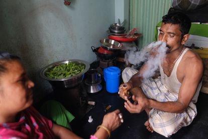 Una mujer fuma marihuana con su babu (novio) en su habitación del prostíbulo de Kandapara, en Tangail.