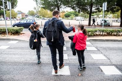 Un padre acompañando a sus hijas a actividades extraescolares en un municipio de la Comunidad de Madrid, en octubre de 2020.