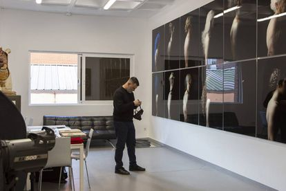 Rafael Díaz, uno de los ocho integrantes de Mala Fama, se prueba una máscara ante un mural fotográfico en su estudio.