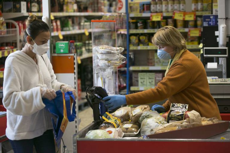 Una cajera atiende a clientes en un supermercado durante el confinamiento.