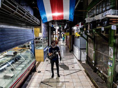 Un trabajador desinfecta el mercado central en San José, Costa Rica.